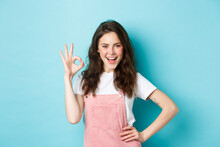 Confident Sassy Girl Showing Okay Sign And Say Yes, Smiling Pleased And Determined, Approve Good Deal, Praising Nice Choice, Like Something Good, Standing Over Blue Background