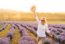 Young Blond Woman Traveller Wearing Straw Hat In Lavender Field Surrounded With Lavender Flowers.