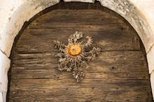 Fleur Séchée De Cardabelle Cloutée Comme Porte-bonheur Sur Une Vieille Porte En Bois Dans Le Village Médiéval De Saint-Guilhem-le-Désert (Occitanie, France)