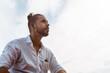 Portret mężczyzny ubranego w białą koszulę patrzący w niebo.