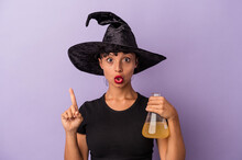 Young Mixed Race Woman Disguised As A Witch Holding Potion Isolated On Purple Background  Having Some Great Idea, Concept Of Creativity.