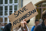 Female activist holding a cardboard sign with text Safe Afghanistan at a demonstration in Lubeck, Germany after the Taliban takeover