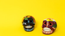 Mexican Clay Skulls, Painted With Colorful Flowers On A Flat Yellow Background