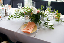 A Table Is Served In A Restaurant With A Beautiful Decor. The Cafe Hall Is Waiting For Guests For A Festive Dinner. The Plate Is Decorated With A Coral Towel, Floating Candles And Flowers