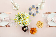 Stylish Table Setting, Cupcakes And Chamomile Flowers On Light Background