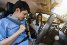 Couple Fastening Seat Belt On Before Driving A Car.