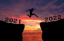 A Young Man Jump Between 2021 And 2022 Years Over The Twilight Sky And Through On The Gap Of Hill  Silhouette Evening Colorful Sky. Happy New Year 2022.
