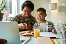 Woman In Military Uniform Sitting At The Table With Her Son And Giving Breakfast To Him