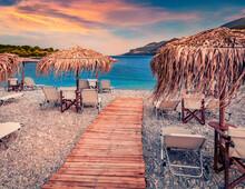 Splendid Summer View Of Fokianos Beach With Wooden Pier And Straw Umbrellas. Astonishing Evening Scene Of Peloponnese Peninsula, Greece, Europe. Marvelous Summer Seascape Of Myrtoan Sea.
