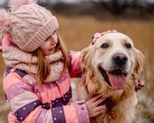 Little Girl Hugging Golden Retriever Dog