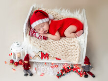 Newborn In Santa Suit Resting On Bed