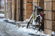 A Bicycle Covered With Ice And Icicles On The Wall Of The Building On The Side Of The Street