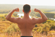 Photo Of The Back Of A Man With Strong Muscles Over A Beautiful Landscape Background.