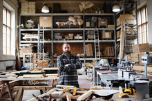 Portrait Of Mature Male Carpenter Standing In Carpentery Workshop, Looking At Camera. Small Business Concept.