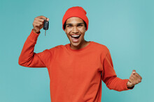 Young Overjoyed Fun Excited Happy African American Man 20s In Orange Shirt Hat Hold Car Key Do Winner Gesture Isolated On Plain Pastel Light Blue Background Studio Portrait. People Lifestyle Concept.