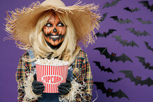 Young Fun Woman With Halloween Makeup Mask In Straw Hat Scarecrow Costume Hold Popcorn Bucket Watch Horror Look Aside Isolated On Plain Dark Purple Background Studio Celebration Holiday Party Concept.