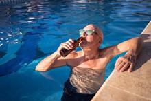 Smiling Man Drinking Beer In Swimming Pool