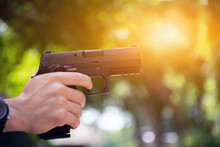 Automatic Black 9mm Pistol Holding In Hands Aming To The Shooting Tar. Concept For Sports, Recreations, Bodyguard, And Security Training Around The World. Soft And Selective Focus.