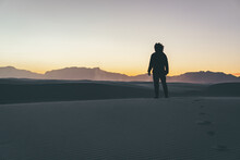 Female Walking In A Desert And Leaving Footsteps On The Sand
