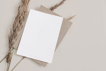 Fall Wedding, Birthday Stationery Composition. Blank Greeting Card, Invitation Mockup With Brown Envelope. Dry Grass, Festuca Plant On Beige Table Background. Autumn Flat Lay, Top View. Copyspace