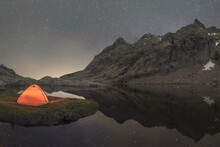 Tent Reflecting In River Against Mount Under Starry Sky