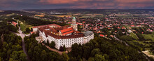 Pannonhalma, Hungary - Aerial Panoramic View Of The Beautiful Millenary Benedictine Abbey Of Pannonhalma (Pannonhalmi Apatsag) With A Purple And Blue Sunset Sky At Summertime