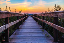 Dramatic Sunset Over Lake And Wooden Walkway With Railing