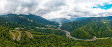 A Large Aerial Panorama Of The Valley Of The Mzymta River (Caucasus) Between The High Mountains, Striped With Green Forest, A Mountain Winding Road To Numerous Hotels By The River. Cloudy Summer Day