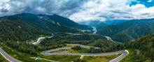 Panorama Of A Mountain Road, Serpentine Descending Down A Forested Slope To The Valley Of The Mzymta River Among The Caucasus Mountains On A Cloudy Summer Day  Russia, Caucasus, Sochi, Summer, Mountai