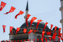 Rows Of Small National Flags Of Turkey Waving In The Wind With The Mosque In The Background