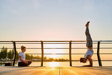 Couple Practicing Acrobatic Yoga Together, Doing Handstand Pose On Nature Outdoors At Sea.