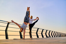 Couple Practicing Acrobatic Handstand Yoga Together On Nature Outdoors At Sea.