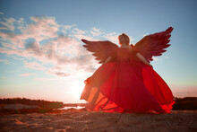 A Plump Blonde Middle-aged Woman With Red Angle Wings In A Desert With Dunes And Sand In A Nice Summer Or Spring Sunny Day With Blue Sky