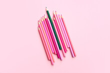Green Pencil Among Pink Ones On Color Background. Concept Of Uniqueness