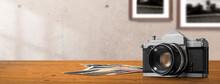木のテーブルの上にあるクラッシックなカメラ、プリントされた古い写真。