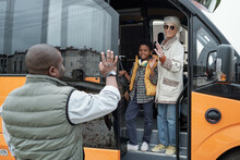 Smiling Black Boy Embraced By Grandmother Waving Hand While Saying Goodbye To Father, They Getting On Bus