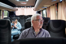 Serious Pensive Senior Passenger In Glasses Sitting I Modern Bus And Looking Out Window