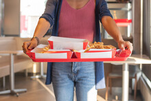 Close Up Portrait Of A Satisfied Pretty Young Woman Walk Holding A Food Tray  Fried Chicken And French Fries, Sparkling Water N The Restaurant. Unhealthy Food Concept, Close Up