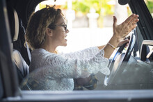 Frustrated Woman Shouting While Driving The Car. Stressed Woman Driving Car In Traffic. Rude Woman Driving Her Car Gesturing With Hand While Arguing With Someone During Daytime Road Traffic