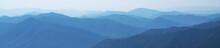 Panorama Of Dark Blue Mountain Landscape In Fog. Horizontal Image. Selective Focus.
