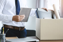 Personnel Packing Personal Belongings And Files Into A Brown Cardboard Box With Resignation Letter For Changing And Resign From Work Concept For Quit Or Change Of Job