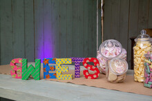 Sweet Jars Filled With Retro Sweets Next To A Sign Reading Sweets