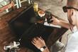 Człowiek pracujący przy laptopie z smartfonem, piszący notatki w zeszycie przy stole.