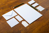 Composition of white cards and envelopes with pencils on wooden background