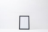 Composition of white card in black frame with copy space on white background