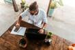 Mężczyzna pracujący przy laptopie z telefonem, praca zdalna podczas podróży, cyfrowy nomada w kawiarni.
