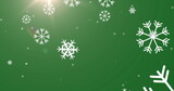 Digital image of snowflakes falling against bright spot of light on green background