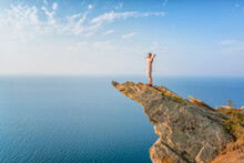 A Happy Young Man With His Hands Raised Stands On A Picturesque Steep Cliff Above The Sea Against The Sky. The Concept Of Travel And Freedom.