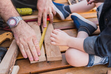 Crop Father With Son Measuring Wooden Plank