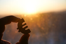 Man's Hand Hold The Euro Icon Silhouette Against Sunny Blue, Yellow Sky. Sun Rays. Euro Sign, Symbol Of Money, Idea Of Euro Union